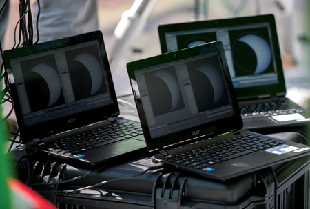 Three laptops display images of a solar eclipse