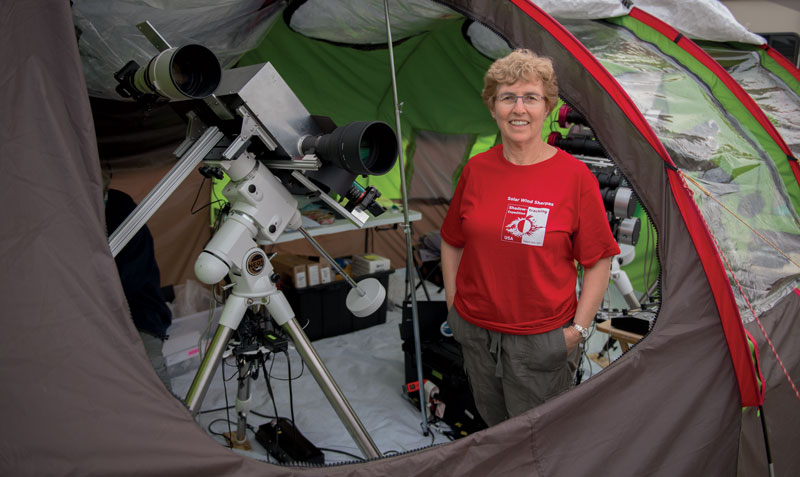 Photo of solar physicist Shadia Habbal inside a tent with a telescope