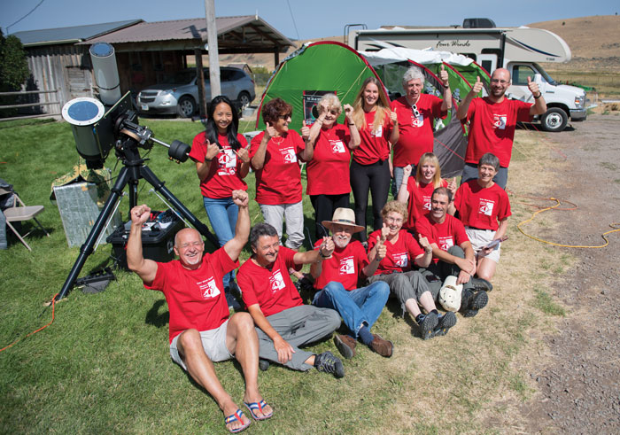 Team of scientists give a thumbs-up in front of tents and telescopes on a rural ranch