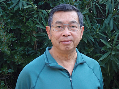 An older Asian man in a teal jacket before a leafy backdrop