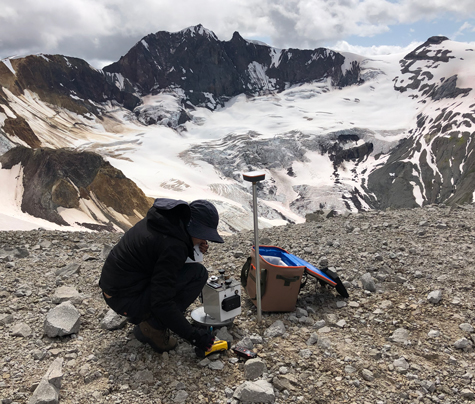 A researcher sets up a gravimeter near a mountain glacier.