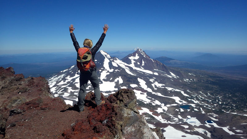 A woman stands on the rocky summit of South Sister in Oregon, raising her hands towards a series of volcanoes to the north, including Middle Sister, North Sister, and Mount Washington.
