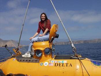 Smiling woman sits atop a small submersible.