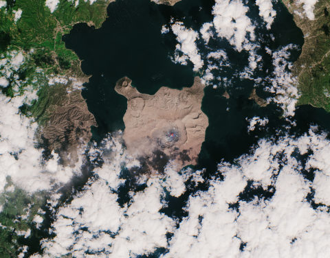 A satellite image of Taal volcano and the surrounding area covered by brown ash