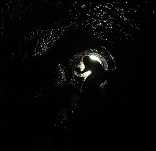 Silhouette of a girl crawling through a lava tube