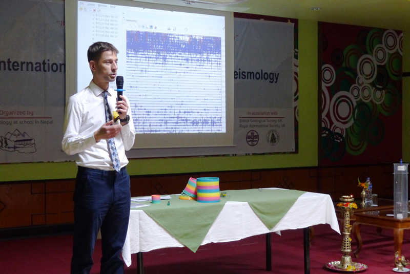 Seismologist György Hetényi lectures in front of a seismometer reading