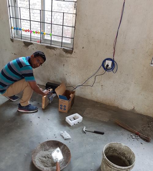 Seismologist Shiba Subedi installs a seismometer in a school in Nepal