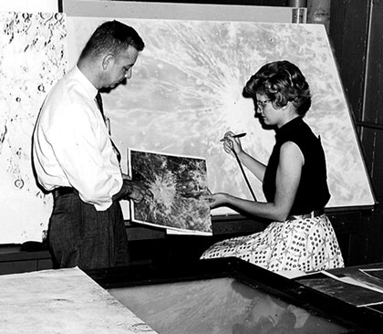 A woman copies a photograph of the Moon's surface onto a map using an airbrush.
