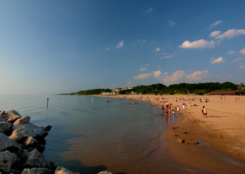 Dozens of beachgoers enjoy a sandy beach and calm swimming area on Lake Michigan.