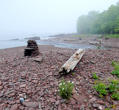 Rounded stones are stacked into a fireplace on a rocky beach on the south shore of Lake Superior.