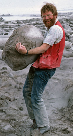 Smiling scientist carries a huge pumice rock in an ashy landscape