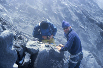 Scientists assess rocks on the top of a smoking volcano.