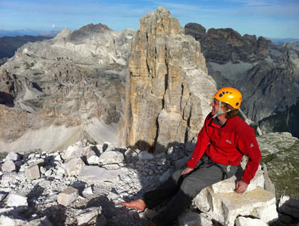 Jörg Robl in a climbing helmet sits at the summit of a high peak