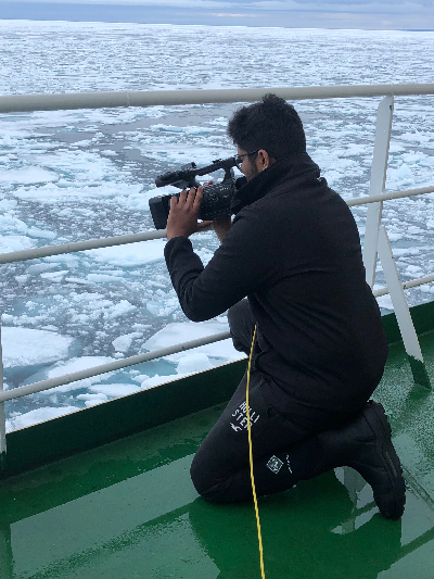 A student shoots video of sea ice from the deck of a ship
