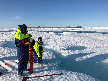 Two students collect ice core samples
