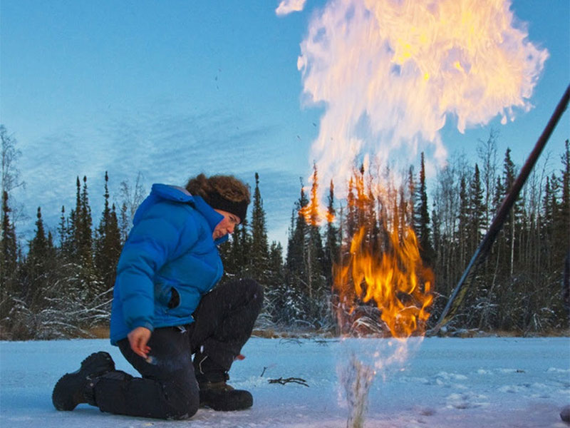 Flames from ignited methane rise from a hole in the ice on a lake