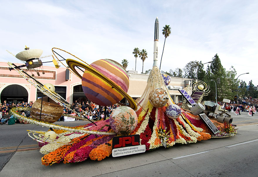 Rose Parade float with a rocket, planets, and satellites