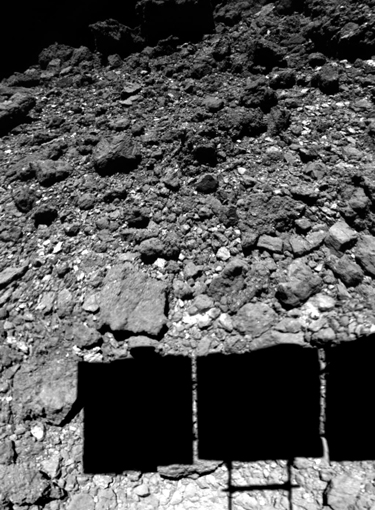 Black-and-white satellite image of a spacecraft, seen in shadow, landing on the rocky surface of the asteroid Ryugu