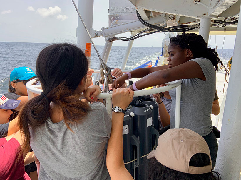 Students work with a water sampling device aboard a research cruise