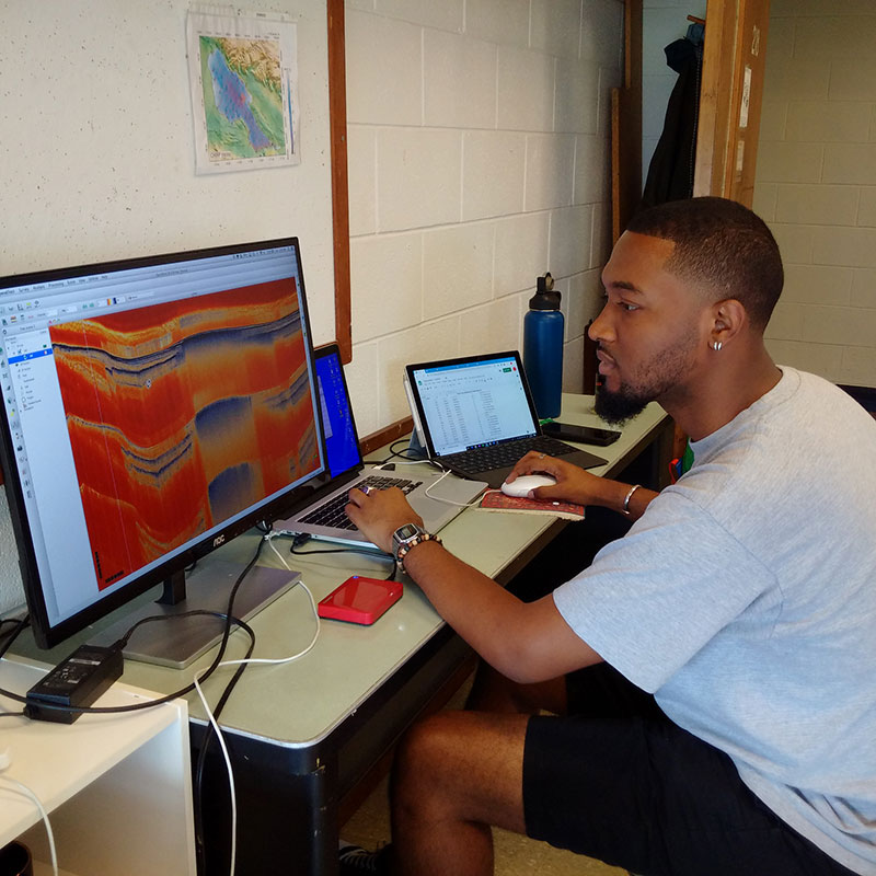 An undergraduate student looks at tectonic profiles on a computer monitor