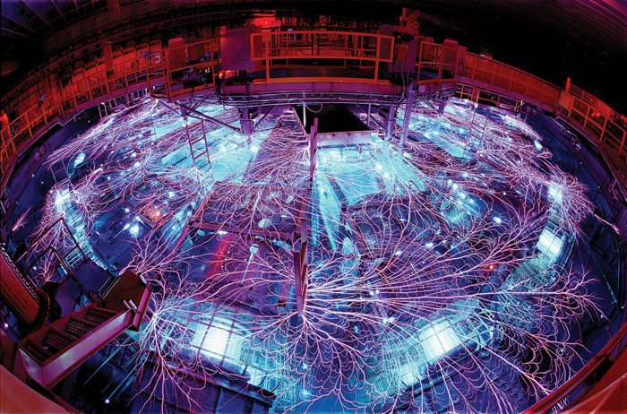 Lavender colored electrical currents arc between parts of a large instrument that glows blue
