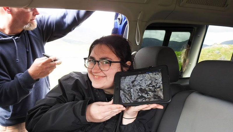 Smiling young woman holds an iPad while sitting in a van