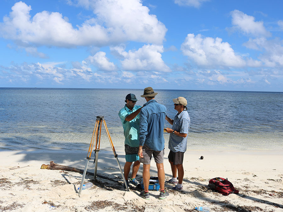The three study authors take measurements on the beach