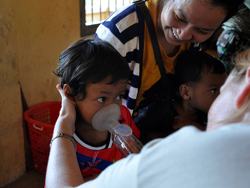 A young girl in Cambodia practices inhaling asthma medication