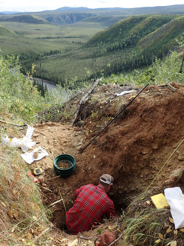 A researcher crouches in a deep pit dug into sediments above the Fortymile River in Alaska