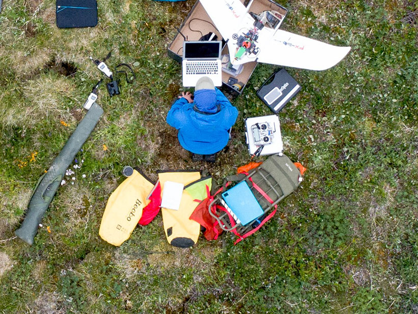 Aerial photo of a seated scientist surrounded by a drone and various instruments on the tundra