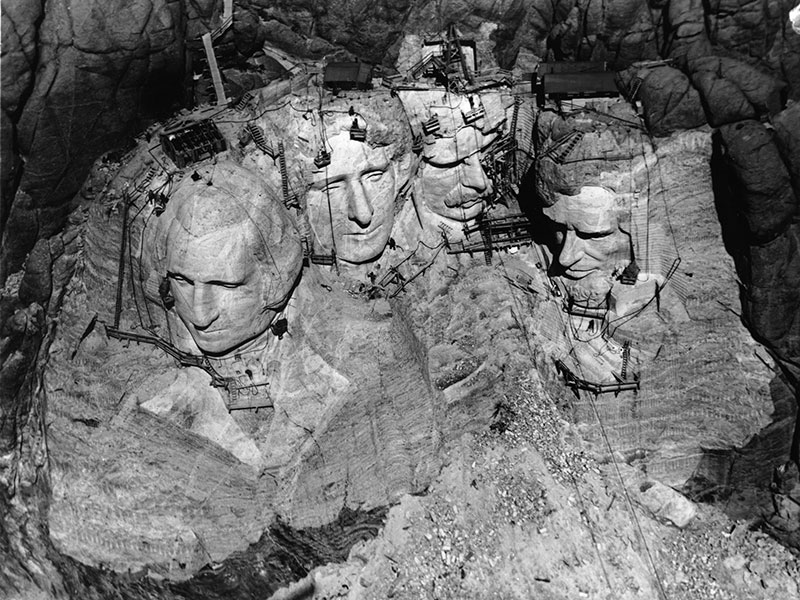 An aerial view of the nearly completed carving on Mount Rushmore shows the scaffolding and ropes used to access the steep face of the mountain.
