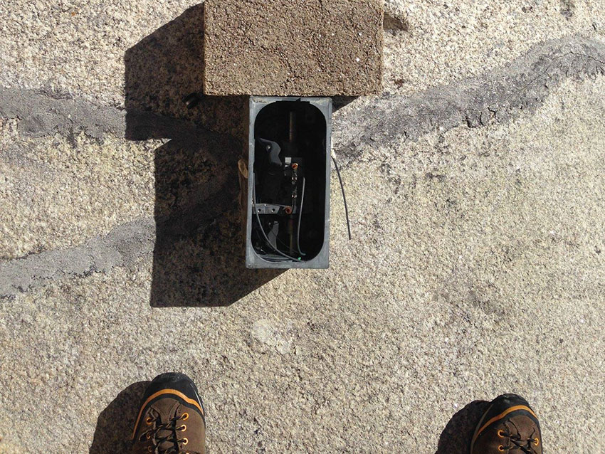 Wires inside a metal box straddle a caulk-sealed crack on the face of Mount Rushmore. A person's shoes appear below the box, as they rappel down the mountain.