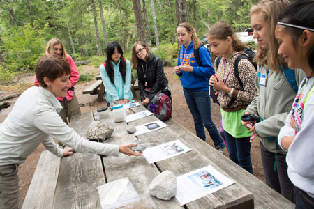 Students look at rock samples and information sheets on a picnic table