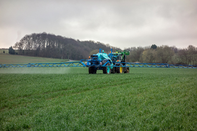 Photograph of a tractor spraying fertilizer on a field