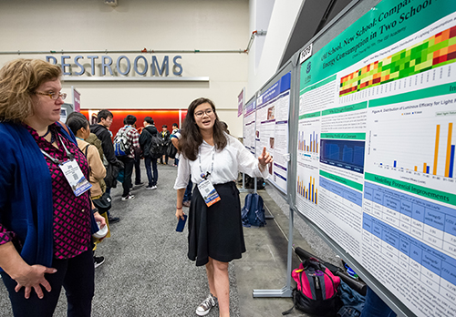 Student explains a poster at a scientific conference.