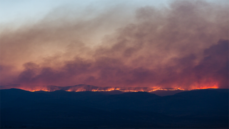 Smoke rises from a line of wildfire burning the landscape in the distance.
