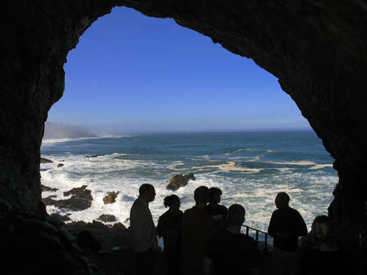Researchers in a cave entrance are silhouetted against the backdrop of Mossel Bay on the central south coast of South Africa.