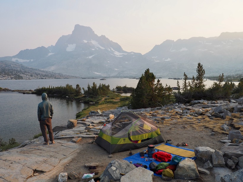 A hiker stands next to a lakeside campsite, looking across Thousand Island Lake to Banner Peak, which is cloaked in smoke.