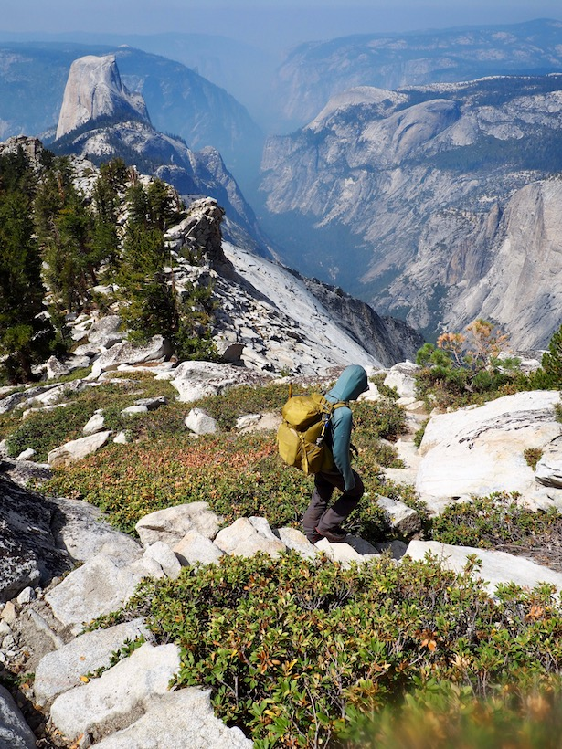A backpacker makes their way down Clouds Rest on a stone staircase, as Half Dome towers over Yosemite Valley.