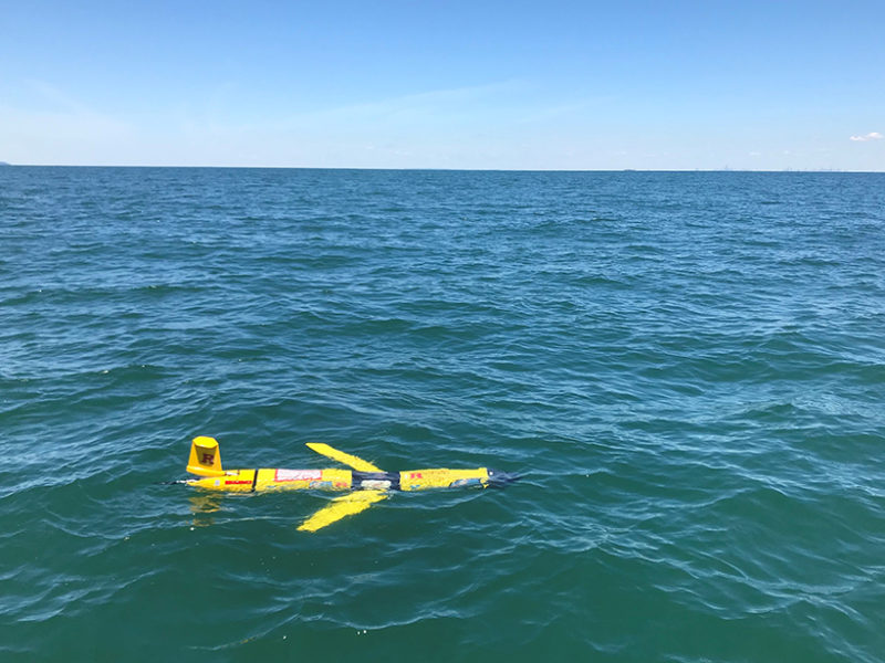 A yellow submarine glider floats on the ocean surface.
