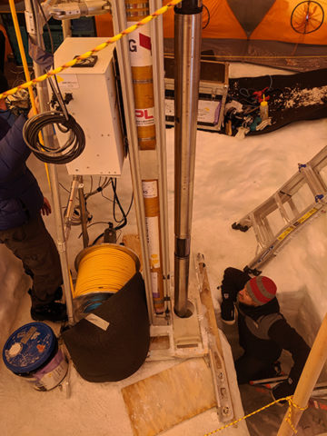 Joey Palmowski of Honeybee Robotics (the company that built the drill) watches as the WATSON in-strument, attached to the drill, is lowered into a borehole