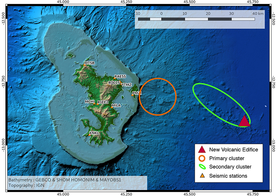 Green island shows the topography of Mayotte, with topographic highs colored brown. The bathymetry of the surrounding ocean is shown in shades of blue, with lighter blue indicator shallower water. The orange circle indicates the primary donut cluster of earthquakes below the possible caldera structure. The green ellipse encloses the secondary cluster parallel to the ridge. The red triangle at the end of the green ellipse denotes the new volcanic edifice.