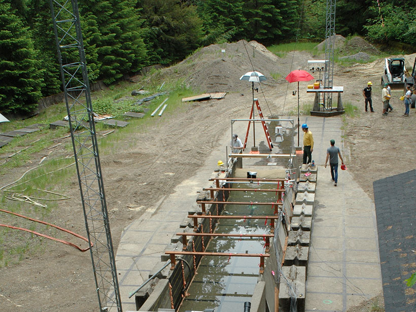 View looking down at the base of the USGS debris flow flume facility showing a makeshift pond and dam