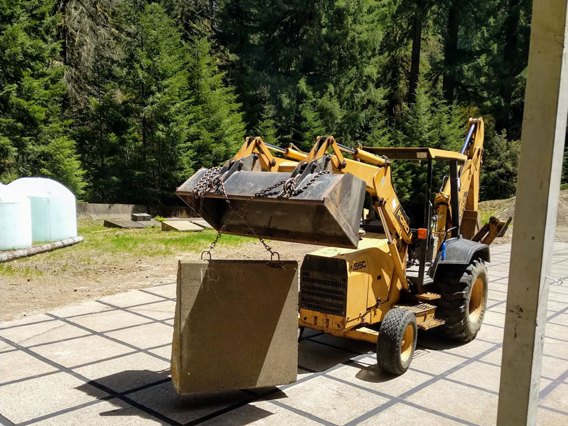A backhoe loader lifts a concrete block using chains.