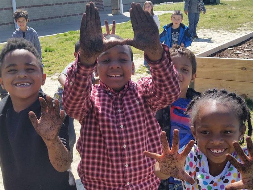 Smiling children display their dirty hands at an urban garden