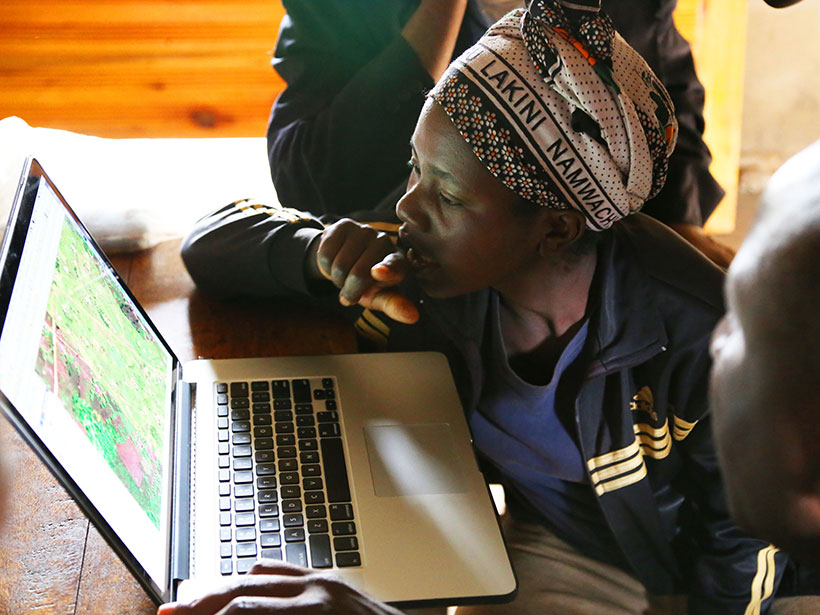 A man and woman study the screen of a laptop.