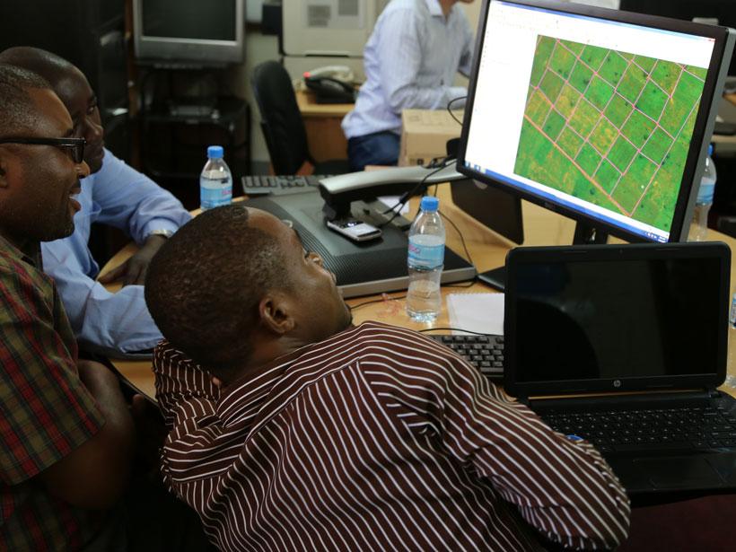 Three men gather around a desktop computer monitor.