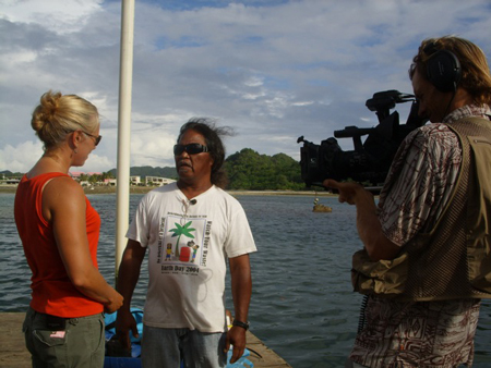 The author conducts an interview on a pier overlooking the water in Palau.