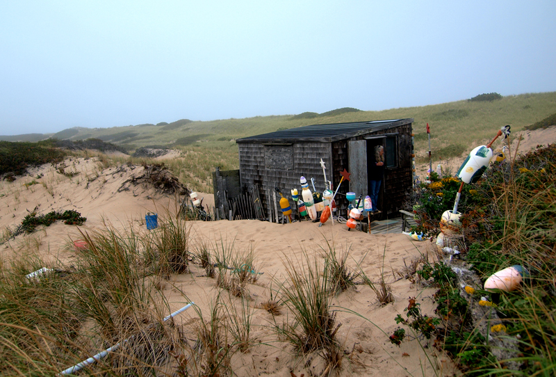 A gray-shingled one-room hut surrounded by grassy sand dunes, where the author spent time in October 2010.