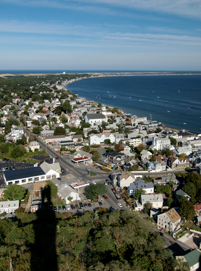 Houses and streets of Provincetown as seen from the town's watchtower, with the Provincetown hook in the background